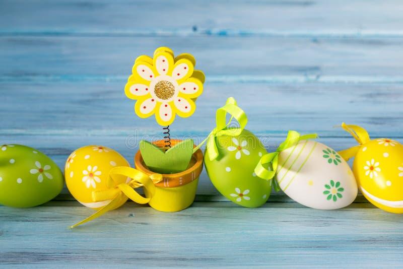 Τα ζωηρόχρωμα αυγά Πάσχας σε μια γραμμή και ένα λουλούδι σημειώνουν τον κάτοχο στο μπλε ξύλινο υπόβαθρο στοκ φωτογραφία