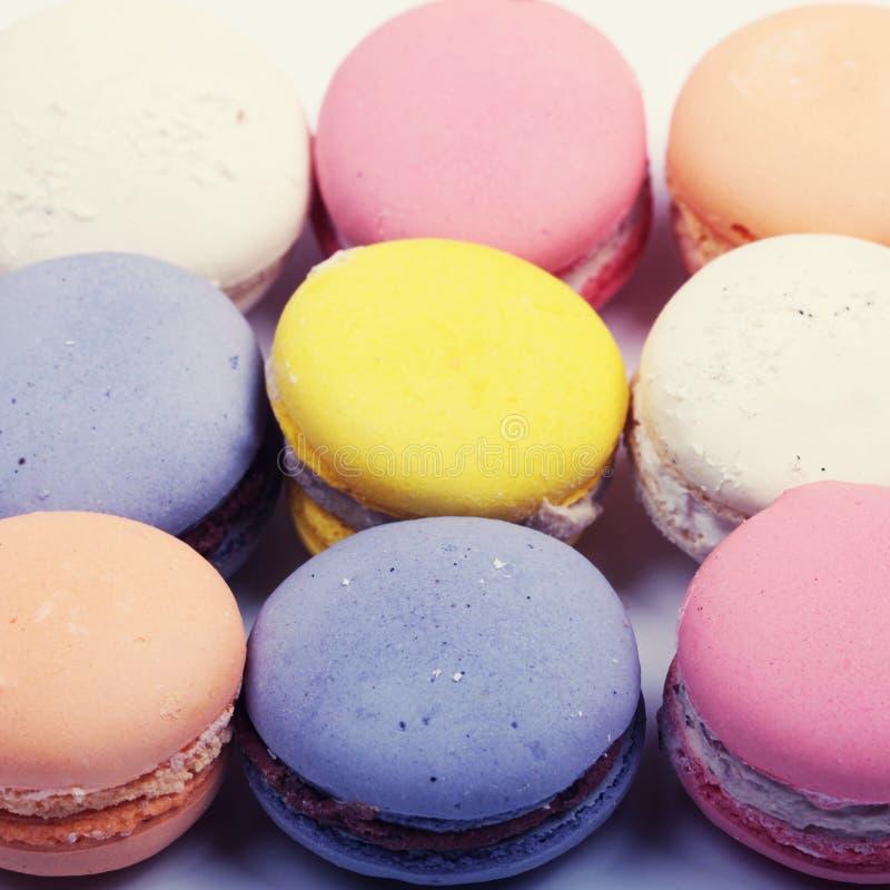 Τα ζωηρόχρωμα γαλλικά μπισκότα macaron κλείνουν επάνω, τετραγωνική εικόνα στοκ εικόνα