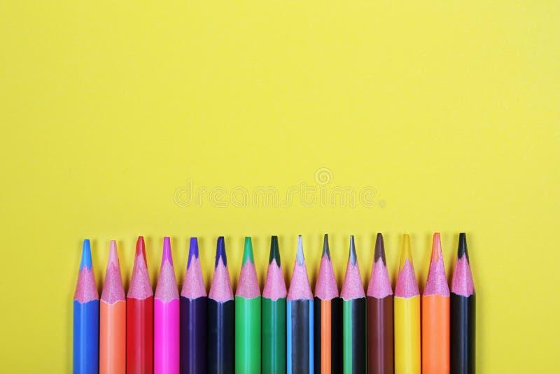 Τα ζωηρόχρωμα μολύβια με το αντίγραφο χωρίζουν κατά διαστήματα στο κίτρινο υπόβαθρο, εκπαίδευση πίσω στο σχολείο, πώληση, έννοια  στοκ φωτογραφίες