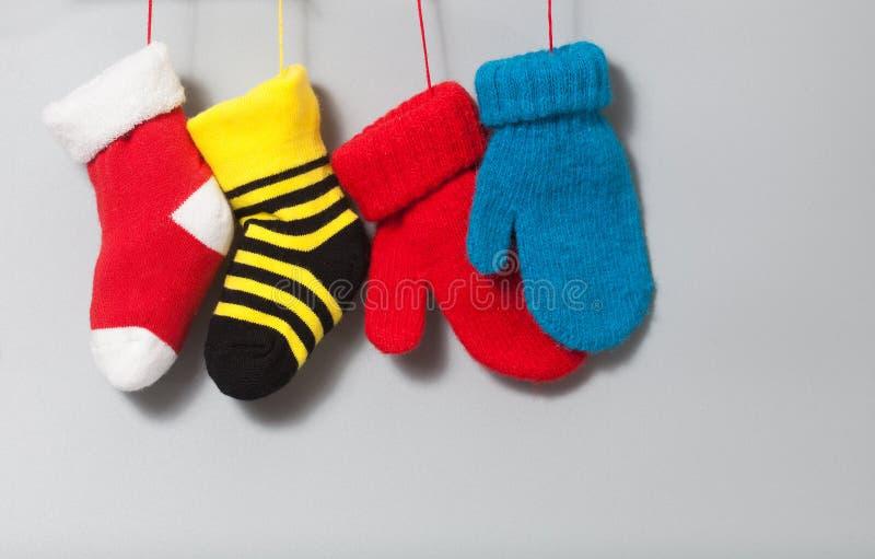 Τα ζωηρόχρωμα Χριστούγεννα γυναικείων καλτσών κτυπούν βίαια τα γάντια στο γκρίζο υπόβαθρο φωτεινό στοιχείο διακοσμήσεων σχεδίου Χ στοκ φωτογραφία