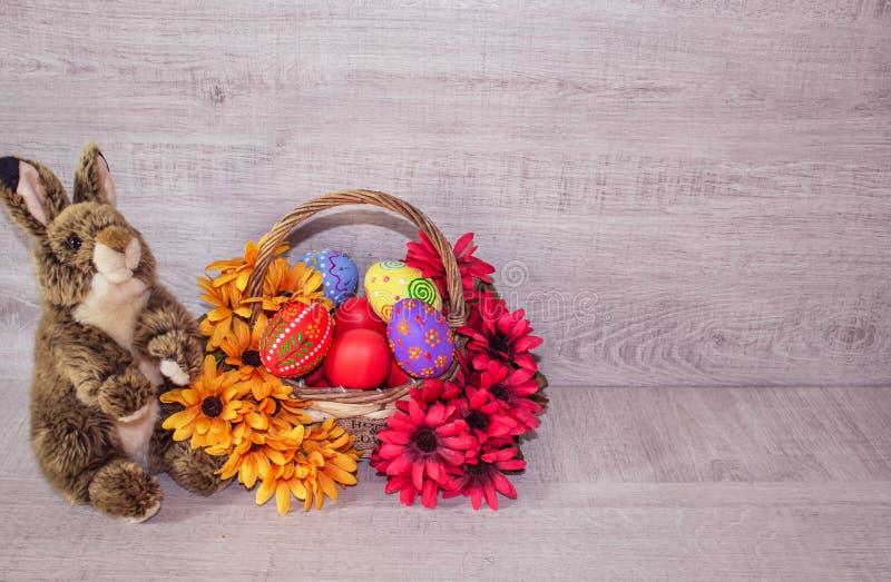 Τα ζωηρόχρωμα χρωματισμένα αυγά Πάσχας βρίσκονται σε ένα καλάθι με τα λουλούδια, σε ένα ξύλινο υπόβαθρο, με ένα χνουδωτό λαγουδάκ στοκ φωτογραφίες