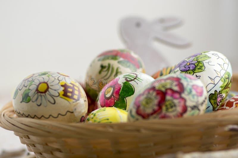 Τα ζωηρόχρωμα χρωματισμένα αυγά Πάσχας στο καφετί ψάθινο καλάθι στους κλάδους, παραδοσιακή ζωή Πάσχας ακόμα, χρωμάτισαν τα λουλού στοκ εικόνα με δικαίωμα ελεύθερης χρήσης