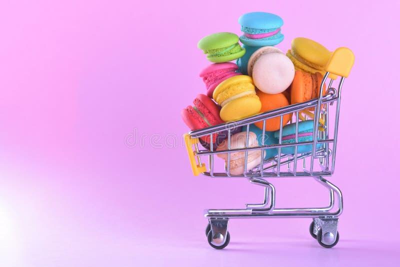 Τα ζωηρόχρωμα macarons ή macaroons στο γλυκό επιδορπίων κάρρων αγορών είναι στοκ φωτογραφία