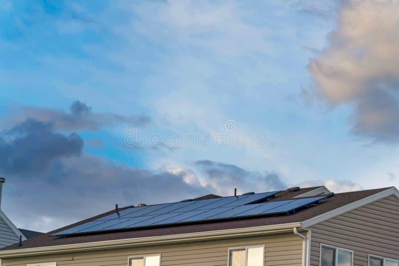 Τα ηλιακά πλαίσια εγκατέστησαν στη στέγη ενός σπιτιού με άσπρα οριζόντια να πλαισιώσουν τοίχων στοκ εικόνες με δικαίωμα ελεύθερης χρήσης