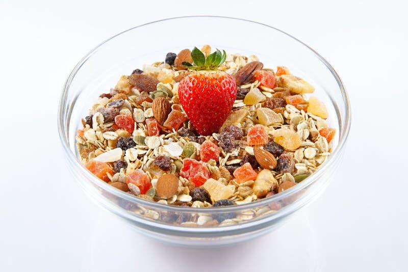 Τα δημητριακά και η φράουλα προγευμάτων, oatmeal με τη φράουλα, τα γλασαρισμένα φρούτα, οι σταφίδες και τα καρύδια σε ένα γυαλί κ στοκ φωτογραφία