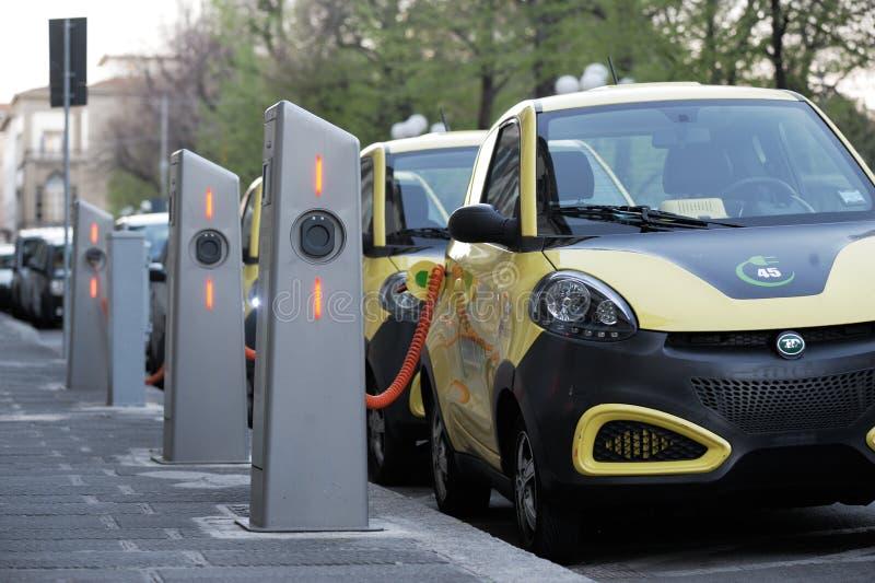 Τα ηλεκτρικά αυτοκίνητα στον ελεύθερο επαναφορτίζοντας σταθμό στοκ φωτογραφίες