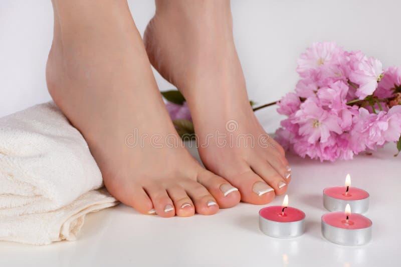 Τα θηλυκά γυμνά πόδια με τα γαλλικά καρφιά γυαλίζουν στην άσπρη πετσέτα και το διακοσμητικό κάψιμο κεριών στον πίνακα και το ρόδι στοκ εικόνες