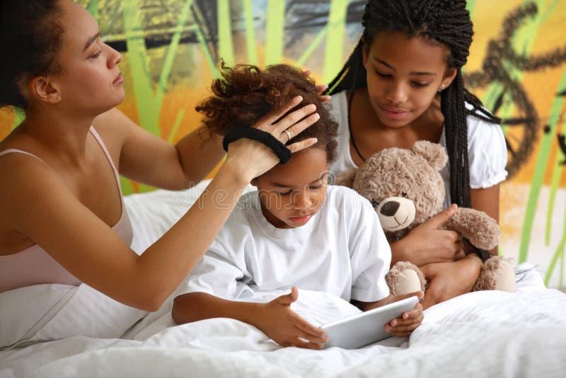 Τα θηλυκά κάνουν hairstyle στην αδελφή της στο κρεβάτι στοκ φωτογραφίες