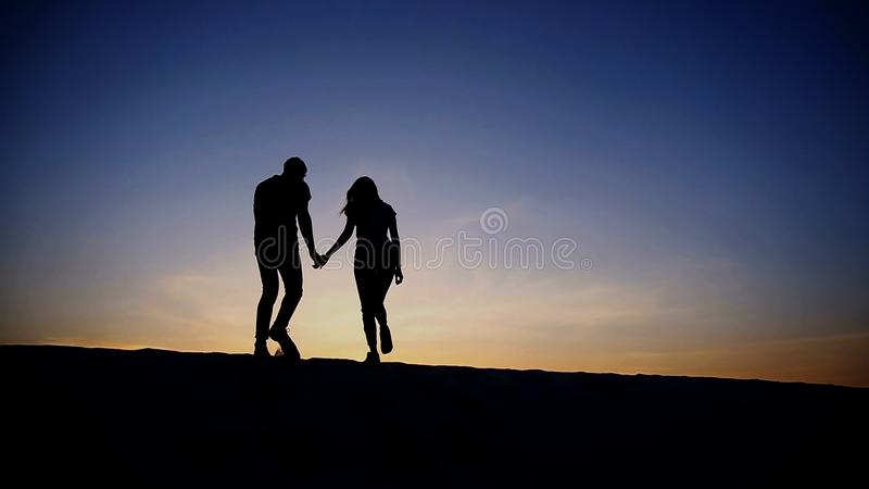 Τα θηλυκά και αρσενικά χέρια εκμετάλλευσης ανέρχονται μαζί στην κορυφή του αμμώδους λόφου στοκ εικόνα με δικαίωμα ελεύθερης χρήσης
