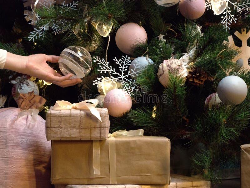 Τα θηλυκά χέρια κρατούν ένα όμορφο παιχνίδι σφαιρών Χριστουγέννων Κιβώτιο δώρων με την άσπρη κορδέλλα, κλάδος ενός δέντρου έλατου στοκ εικόνες