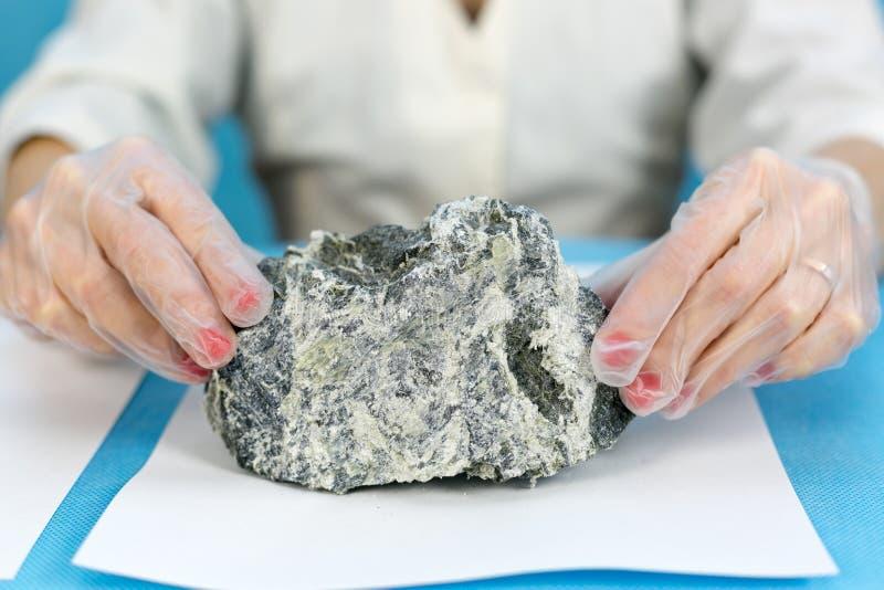 Τα θηλυκά χέρια κρατούν τον επικίνδυνο ορυκτό αμίαντο στοκ φωτογραφίες