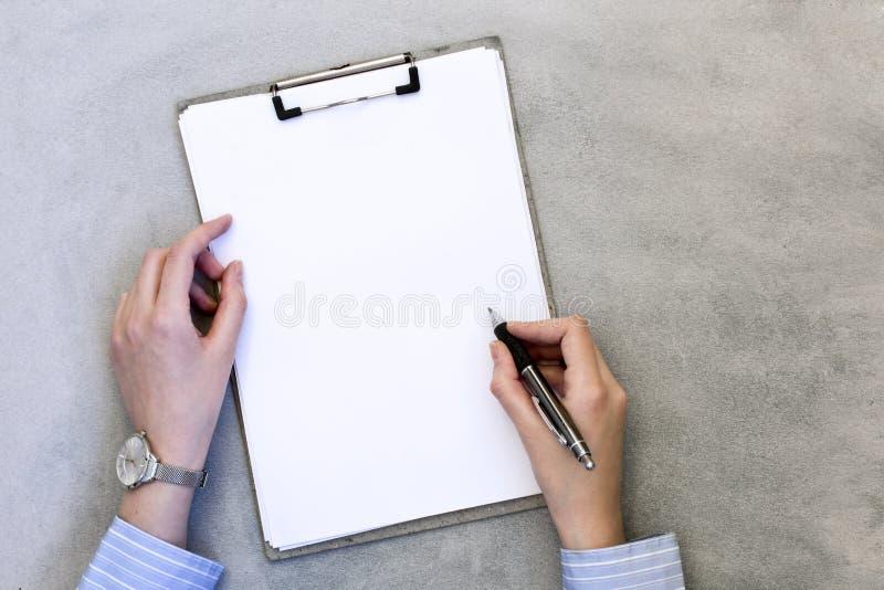 Τα θηλυκά χέρια παίρνουν τις σημειώσεις για το γκρίζο υπόβαθρο στοκ φωτογραφία