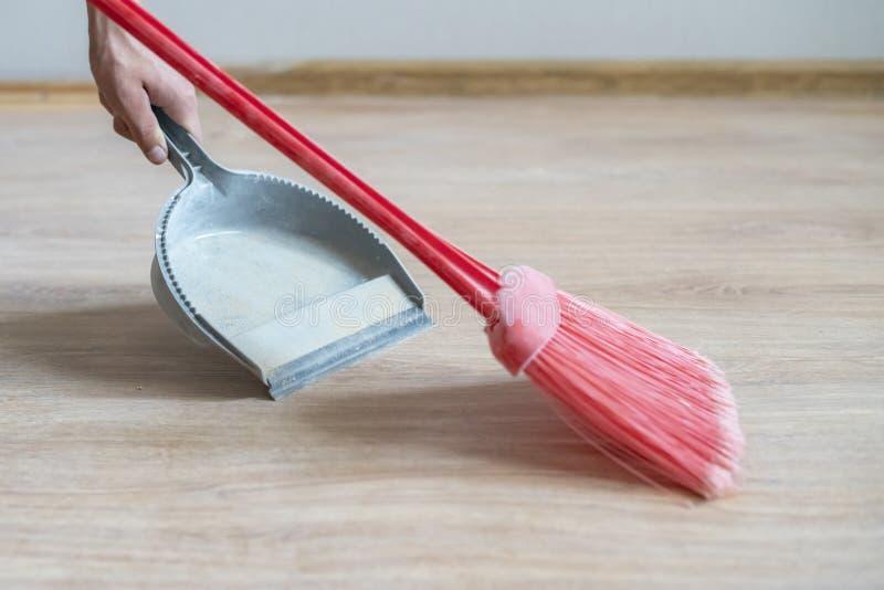 Τα θηλυκά χέρια σκουπίζουν τη σκόνη με τη σκούπα και dustpan στο ξύλινο πάτωμα στο σπίτι φ στοκ εικόνες