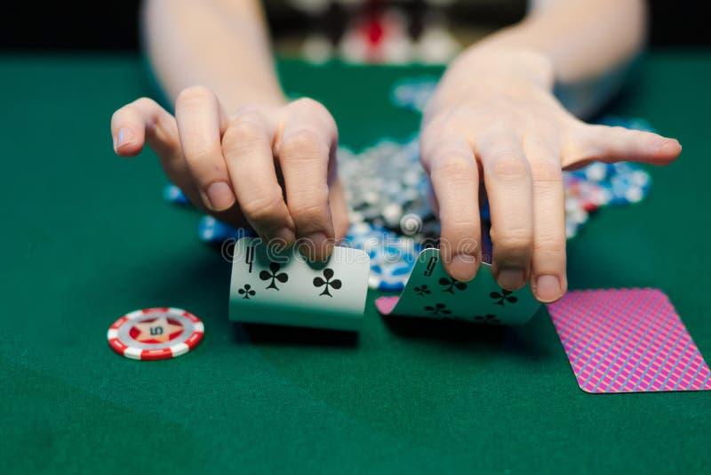 Τα θηλυκά χέρια σχεδιάζουν τις κάρτες και τα τσιπ παιχνιδιού σε μια χα στοκ εικόνες