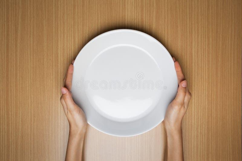 Τα θηλυκά χέρια κρατούν ένα κενό άσπρο πιάτο στοκ φωτογραφίες
