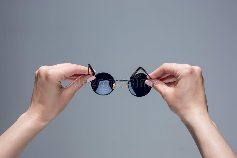 Τα θηλυκά χέρια που κρατούν τα γυαλιά ηλίου στο γκρίζο υπόβαθρο στοκ εικόνες