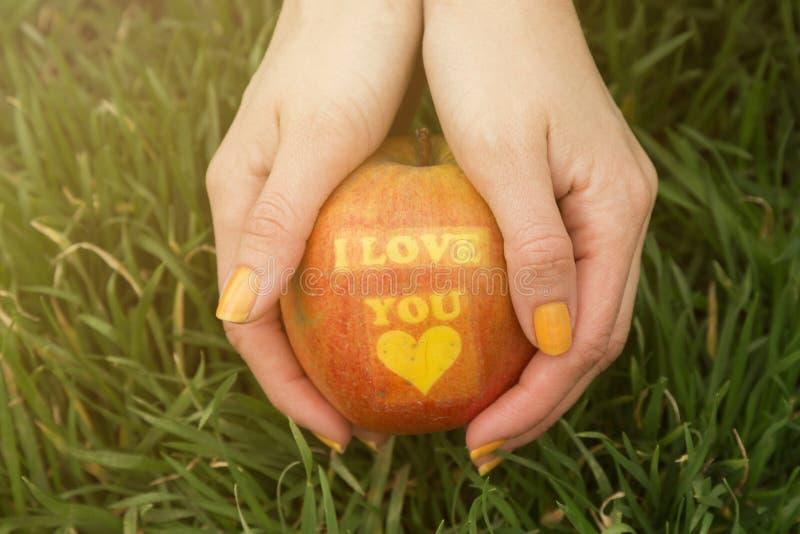 Τα θηλυκά χέρια που κρατούν το μήλο με τυπώνουν σ' αγαπώ στοκ εικόνες
