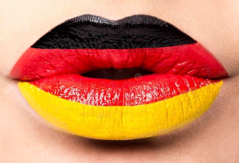 Τα θηλυκά χείλια κλείνουν επάνω με μια σημαία εικόνων της Γερμανίας Μαύρος, κόκκινος, κίτρινος στοκ φωτογραφία με δικαίωμα ελεύθερης χρήσης