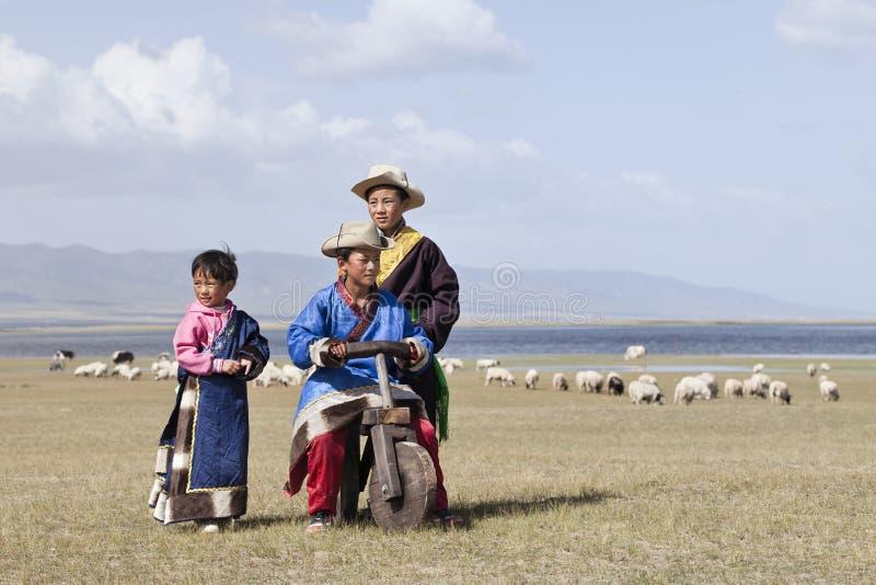 Τα θιβετιανά παιδιά παίζουν κοντά στη λίμνη Qinghai, Κίνα στοκ φωτογραφίες