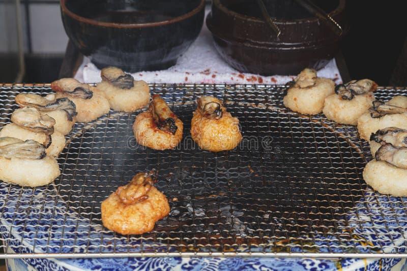Τα ιαπωνικά τρόφιμα οδών έψησαν το ρύζι με το στρείδι στην κορυφή με τη σπιτική σάλτσα σόγιας στη σχάρα στοκ εικόνες με δικαίωμα ελεύθερης χρήσης