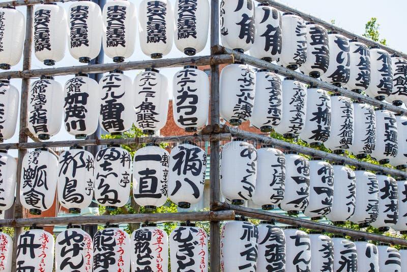 Τα ιαπωνικά φανάρια εγγράφου παράταξαν στα σύνολα μπαμπού με τις ιαπωνικές γραφές και κρεμούν εκτός από έναν ναό στο Τόκιο, Ιαπων στοκ εικόνα