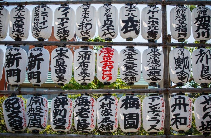 Τα ιαπωνικά φανάρια εγγράφου παράταξαν στα σύνολα μπαμπού με τις ιαπωνικές γραφές και κρεμούν εκτός από έναν ναό στο Τόκιο, Ιαπων στοκ εικόνες