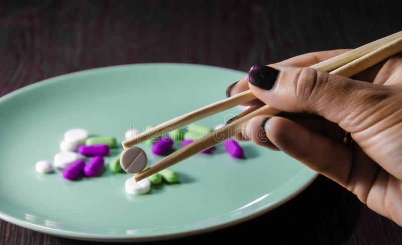 Τα ιατρικά χάπια χρησιμοποιούνται με ξυλάκια σε σκούρο φόντο στοκ εικόνα