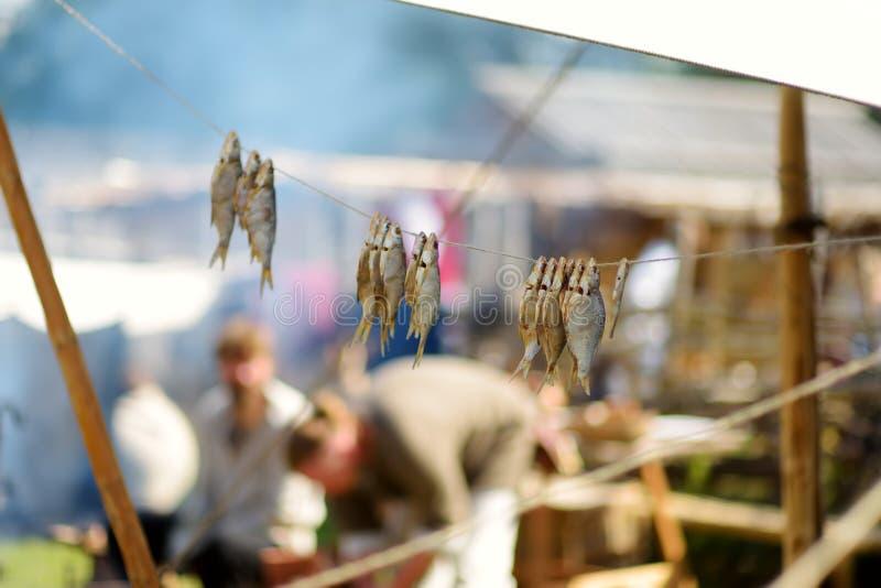 Τα ιστορικά ενεργά στελέχη αναπαράστασης που προετοιμάζουν τα τρόφιμα πέρα από ανοίγουν πυρ του ετήσιου μεσαιωνικού φεστιβάλ, που στοκ εικόνες