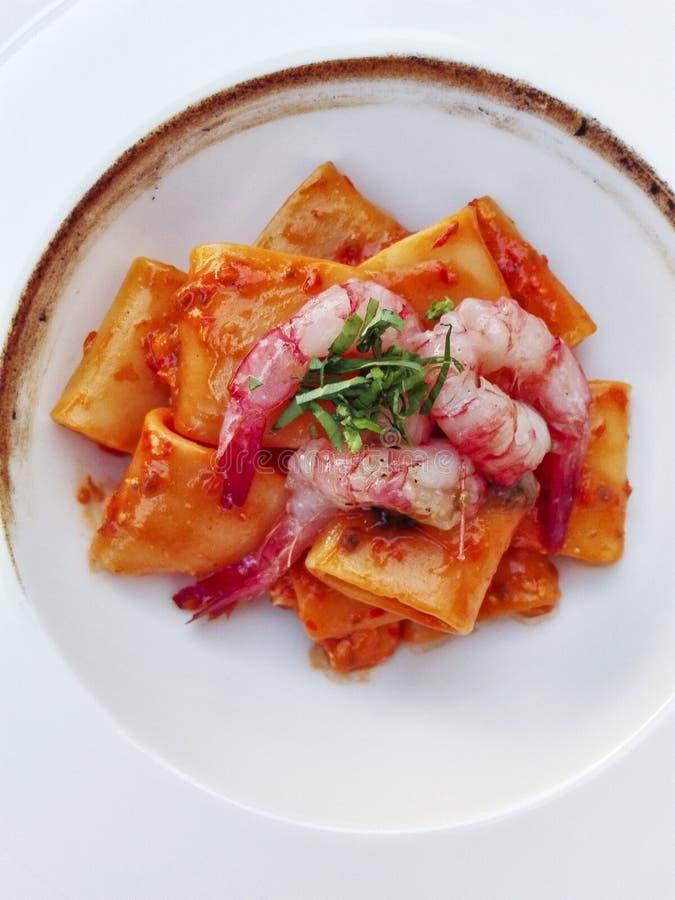 Τα ιταλικά παραδοσιακά κοντά ζυμαρικά paccheri από το gragnano με τις γαρίδες και τα μμένα κρεμμύδια αποβουτυρώνουν στοκ εικόνα με δικαίωμα ελεύθερης χρήσης