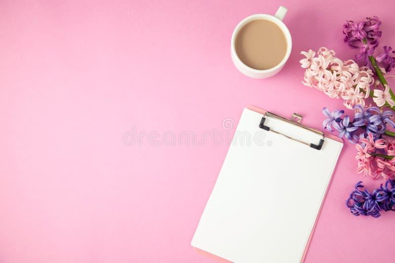 Τα ιώδη λουλούδια, coffe και το σημειωματάριο σε μια ιώδη άνοιξη υποβάθρου, επίπεδο θερινής έννοιας βάζουν τη τοπ άποψη Copyspace στοκ εικόνες