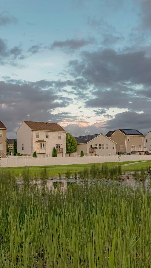 Τα κάθετα σπίτια πλαισίων με τα μπαλκόνια και μια άποψη της χλοώδους λίμνης γεφυρώνουν και επεκτατικός πράσινος τομέας στοκ εικόνες με δικαίωμα ελεύθερης χρήσης