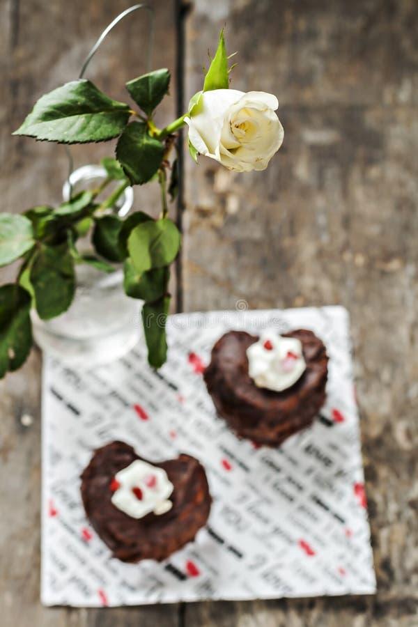 τα κέικ υπό μορφή καρδιάς και λευκού αυξήθηκαν στοκ φωτογραφίες