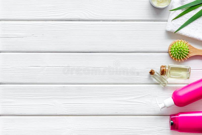 Τα καλλυντικά για την τρίχα φροντίζουν με jojoba, argan ή καρύδων το πετρέλαιο στο μπουκάλι στο άσπρο ξύλινο πρότυπο άποψης υποβά στοκ εικόνες με δικαίωμα ελεύθερης χρήσης
