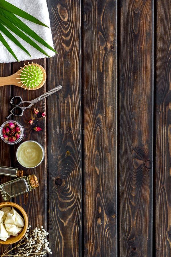 Τα καλλυντικά για την τρίχα φροντίζουν με jojoba, argan ή καρύδων το πετρέλαιο στο μπουκάλι στο ξύλινο πρότυπο άποψης υποβάθρου τ στοκ εικόνα