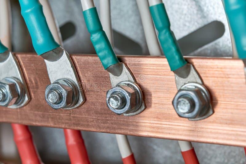 Τα καλώδια ή τα καλώδια συνδέονται με την ηλεκτρική μπάρα τροφοδότησης με τη βοήθεια lugs καλωδίων στοκ φωτογραφία
