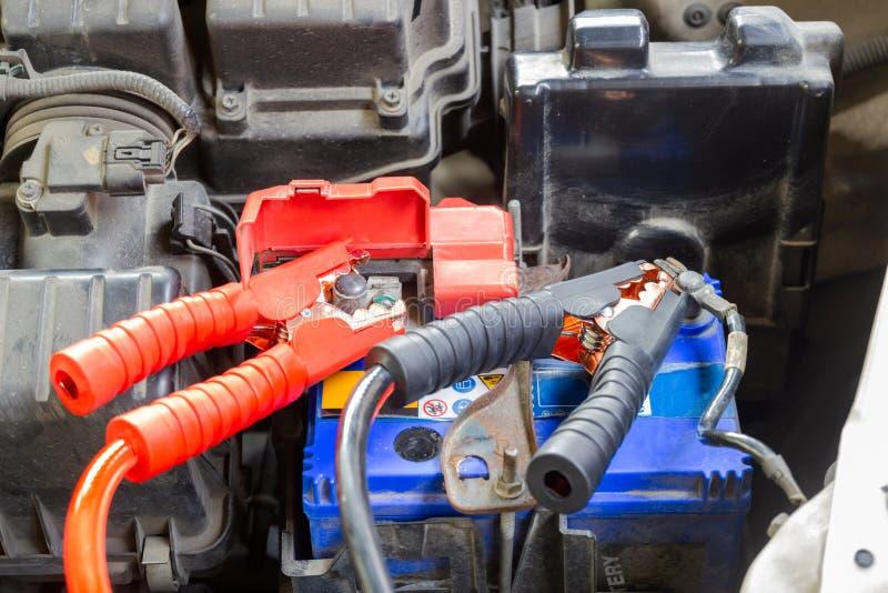 Τα καλώδια αλτών για τη φόρτιση της μπαταρίας οχημάτων προσδιορίζουν θετικός και αρνητικός στοκ εικόνες