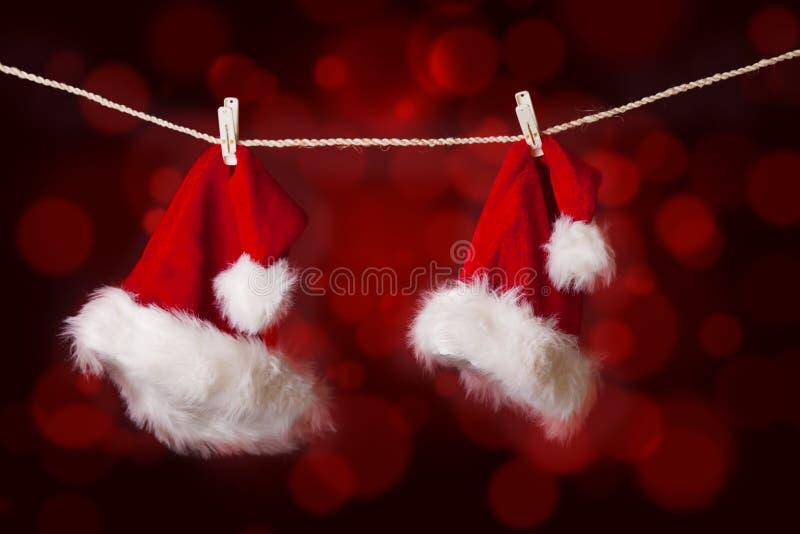 Τα καπέλα Santa που κρεμούν στο κόκκινο τα φω'τα στοκ φωτογραφία