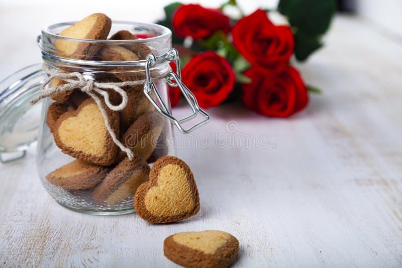 Τα καρδιά-διαμορφωμένα μπισκότα σε ένα βάζο γυαλιού και κόκκινος αυξήθηκαν στοκ φωτογραφία με δικαίωμα ελεύθερης χρήσης