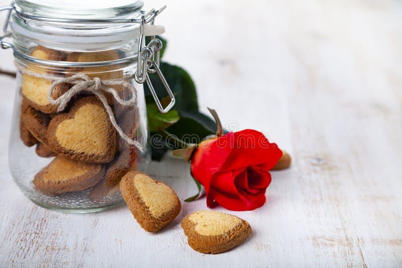 Τα καρδιά-διαμορφωμένα μπισκότα σε ένα βάζο γυαλιού και κόκκινος αυξήθηκαν στοκ εικόνα με δικαίωμα ελεύθερης χρήσης