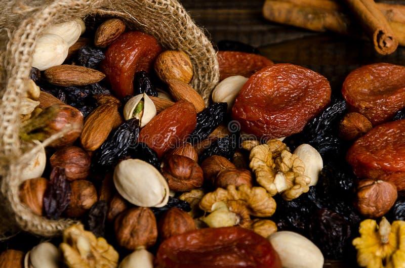 Τα καρύδια, οι ξηροί καρποί, τα φυστίκια και άλλο διασκόρπισαν από την τσάντα στον πίνακα στοκ φωτογραφίες με δικαίωμα ελεύθερης χρήσης