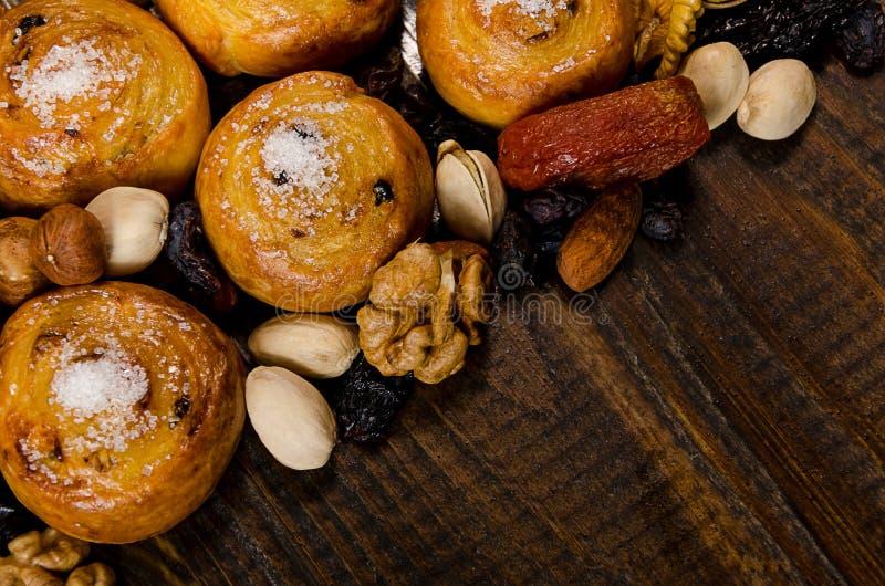 Τα καρύδια, οι ξηροί καρποί, τα φυστίκια και τα σπιτικά μπισκότα διασκόρπισαν από την τσάντα στον πίνακα με μια θέση για το γράψι στοκ εικόνα