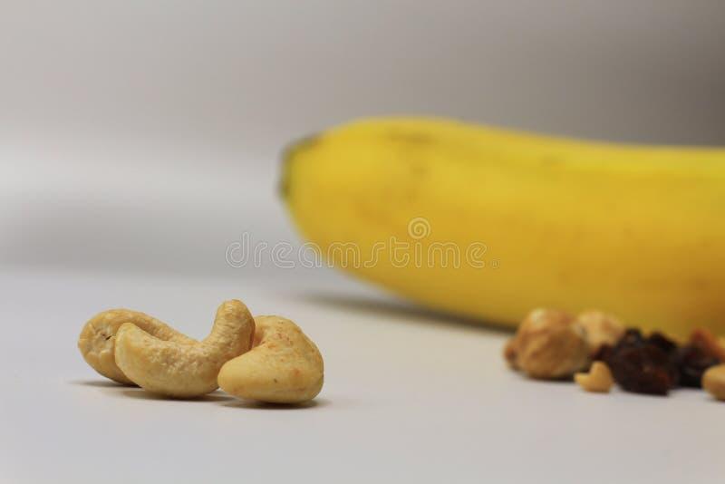 Τα καρύδια των δυτικών ανακαρδίων κλείνουν επάνω με άλλα καρύδια και φρούτα ως υπόβαθρο στοκ φωτογραφία με δικαίωμα ελεύθερης χρήσης