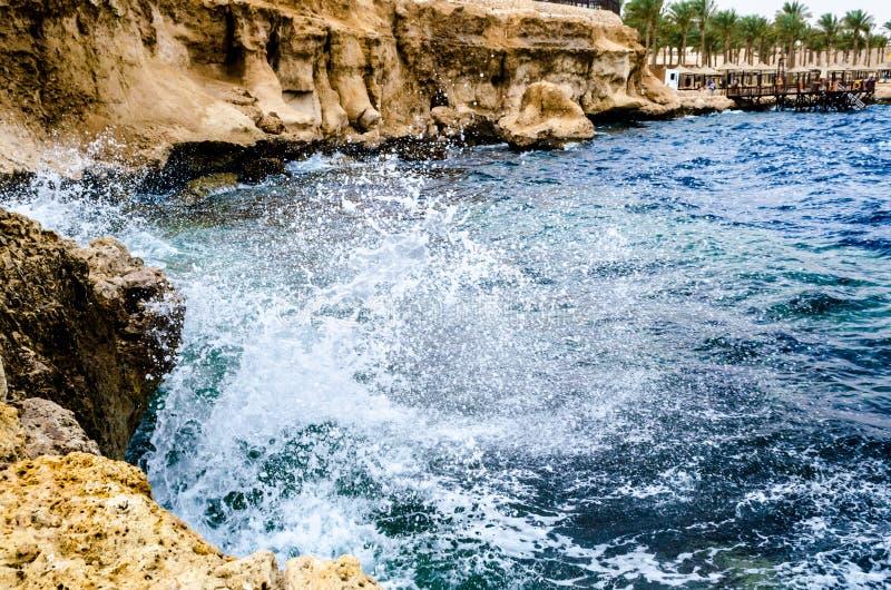 Τα καταβρέχοντας κύματα της κυματωγής που συντρίβει ενάντια στους βράχους είναι στοκ φωτογραφία με δικαίωμα ελεύθερης χρήσης