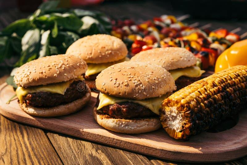 Τα καυτά εύγευστα burgers και τα λαχανικά που ψήνονται στη σχάρα για ψήνουν υπαίθρια στοκ εικόνα