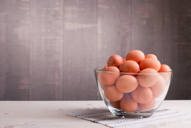 Τα καφετιά αυγά σε ένα μεγάλο γυαλί κυλούν σε έναν ελαφρύ ξύλινο πίνακα και το s στοκ εικόνες