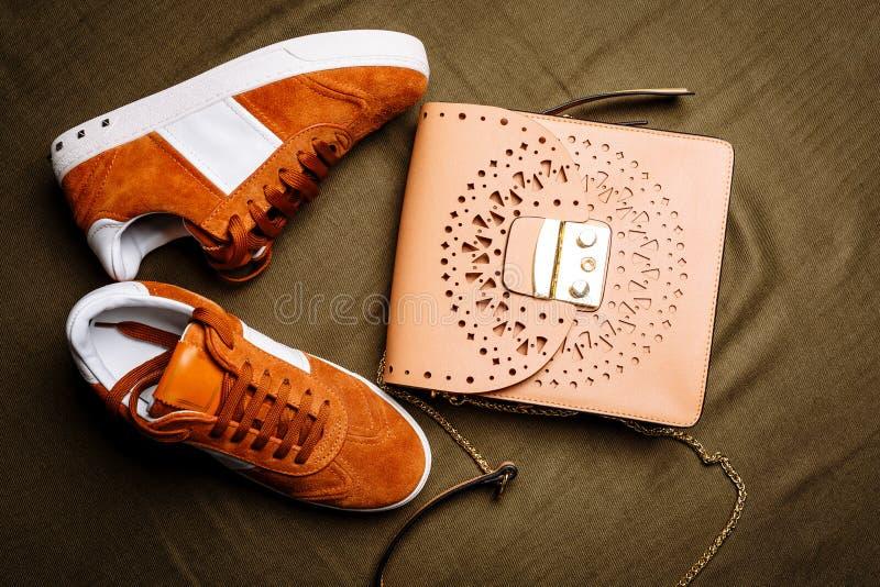 Τα καφετιά πάνινα παπούτσια σουέτ με τις άσπρες εμφάσεις σε ένα άσπροι μόνο και καφετί δέρμα τοποθετούν σε σάκκο με μια χρυσή κλε στοκ εικόνες