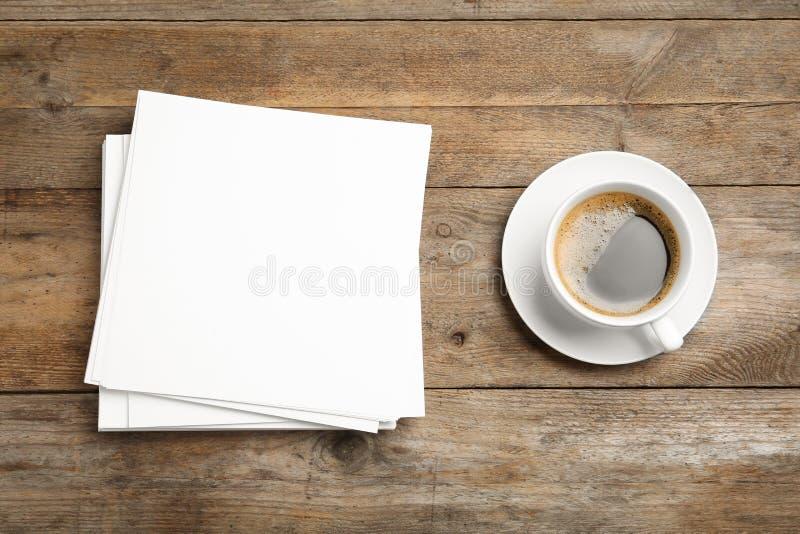 Τα κενά φύλλα εγγράφου για τον καφέ φυλλάδιων και φλυτζανιών στο ξύλινο υπόβαθρο, επίπεδο βάζουν r στοκ φωτογραφία με δικαίωμα ελεύθερης χρήσης