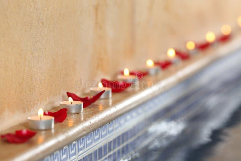 Τα κεριά και αυξήθηκαν πέταλα σε ένα poolside SPA χαλαρώνουν την έννοια στοκ φωτογραφίες