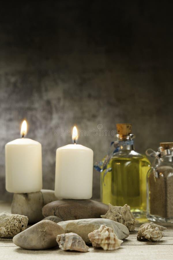 Τα κεριά που καίνε στις πέτρες με τα θαλασσινά κοχύλια και το ουσιαστικό πετρέλαιο στον ξύλινο πίνακα και το γκρίζο υπόβαθρο στοκ εικόνα με δικαίωμα ελεύθερης χρήσης