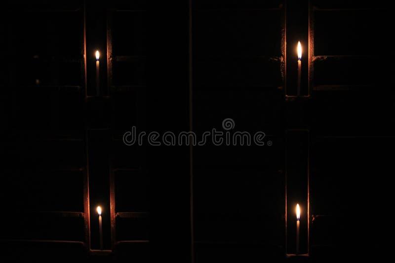 Τα κεριά φλογών θεωρούν την έννοια Κεριά σε ένα κλουβί στοκ εικόνα με δικαίωμα ελεύθερης χρήσης